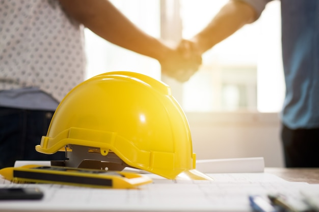 Concetto di lavoro di squadra, gruppo di architettura che stringe mano nel constraction della costruzione