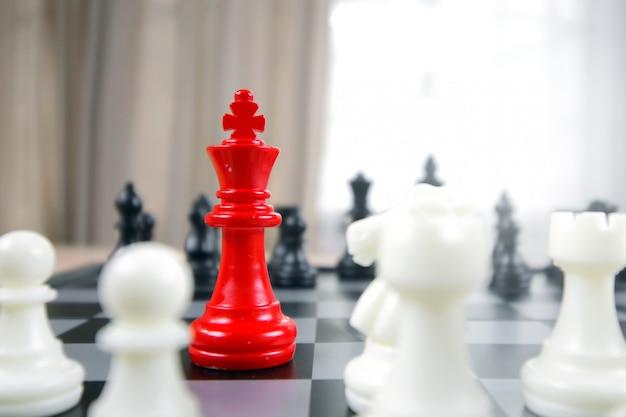 Concetto di leadership di scacchi con re rosso e scacchi bianchi e neri
