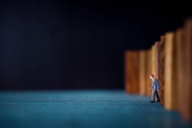 Concetto di leadership. figura in miniatura dell'uomo d'affari che fa un passo in avanti