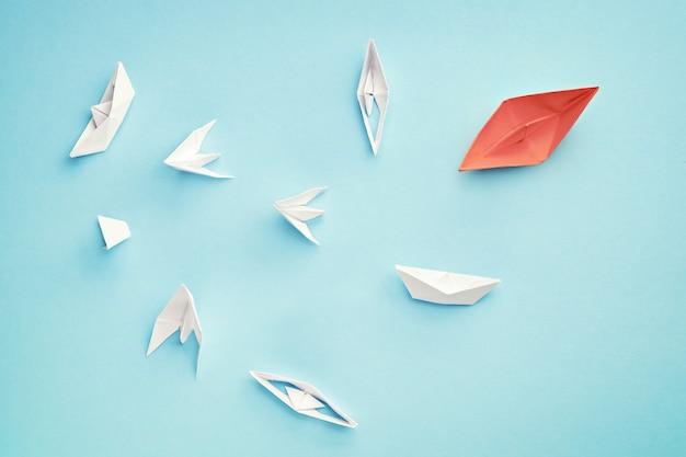 Concetto di leadership senza successo. barca di carta rossa e molte navi che affondano
