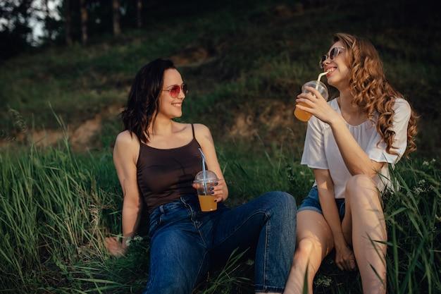 Concetto di lifestyle: due amiche emotive sono allegre, si siedono sull'erba, bevono cocktail in occhiali da sole, al tramonto, espressione facciale positiva, all'aperto