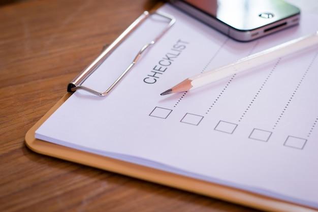 Concetto di lista di controllo - lista di controllo, carta e una penna con la parola di lista di controllo sulla tavola di legno