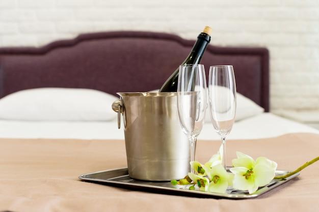 Concetto di luna di miele. secchiello per champagne vicino al letto in una camera d'albergo