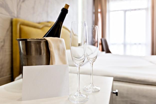 Concetto di luna di miele. secchio di champagne vicino al letto in una stanza d'albergo