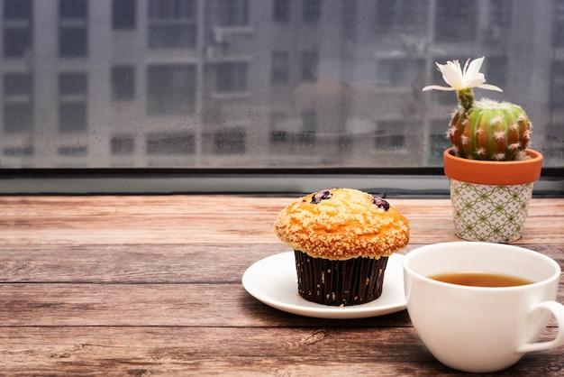 Concetto di lunedì mattina, tè caldo e torta del muffin su area di lavoro di legno