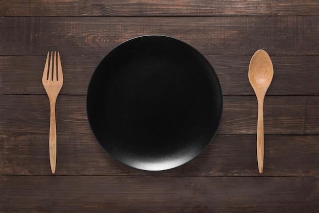 Concetto di mangiare. cucchiaio, forchetta e piatto nero sui precedenti di legno