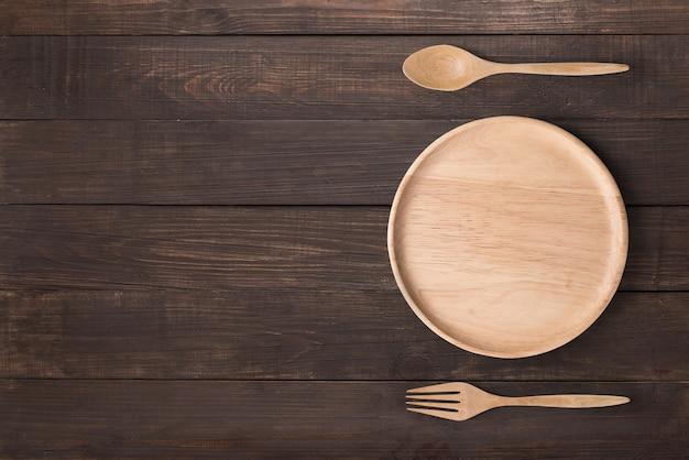 Concetto di mangiare. il piatto di legno, il cucchiaio di legno e la forchetta di legno hanno messo sui precedenti di legno
