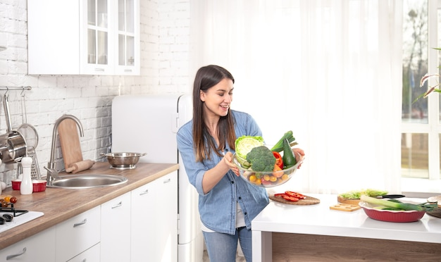 Concetto di mangiare sano. giovane bella donna in cucina con frutta e verdura. cibo vegano