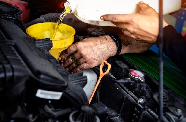 Concetto di manutenzione dell'automobile meccanico di automobile che sostituisce e che versa olio fresco nel motore alla stazione di servizio di manutenzione. il tecnico di riparazione automatico versa il nuovo olio per sostituire quello vecchio