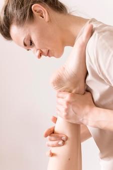 Concetto di massaggio alla caviglia del primo piano