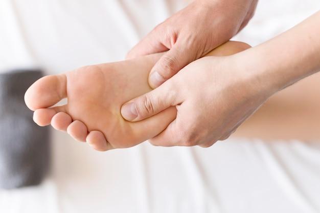 Concetto di massaggio del piede del primo piano