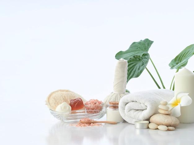 Concetto di massaggio della stazione termale, palla di erbe della compressa, crema, sapone del fiore, candela profumata e sale rosa himalayano, isolato su bianco