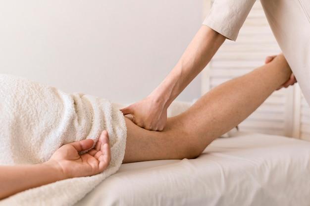 Concetto di massaggio delle gambe del primo piano