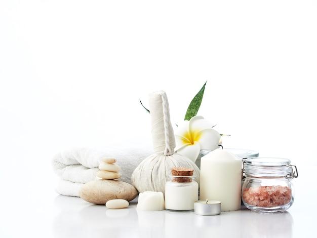 Concetto di massaggio spa, palla impacco alle erbe, crema, sapone ai fiori, candela profumata e sale rosa dell'himalaya, isolato