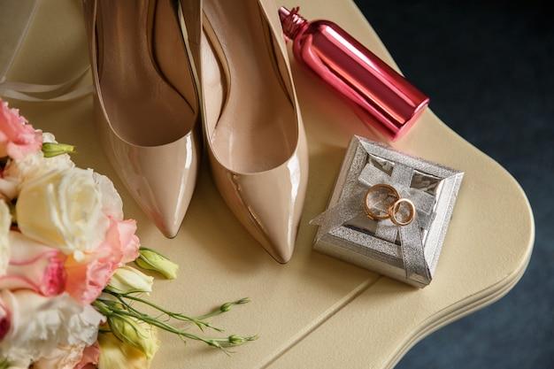 Concetto di matrimonio. accessori da sposa: fedi nuziali su scatola degli anelli, scarpe da sposa su tacchi alti, bottiglia di profumo rosa vicino al bouquet da sposa