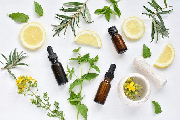 Concetto di medicina alternativa, cosmetici naturali, erbe, limone, oli, mortaio e pestello, distesi.