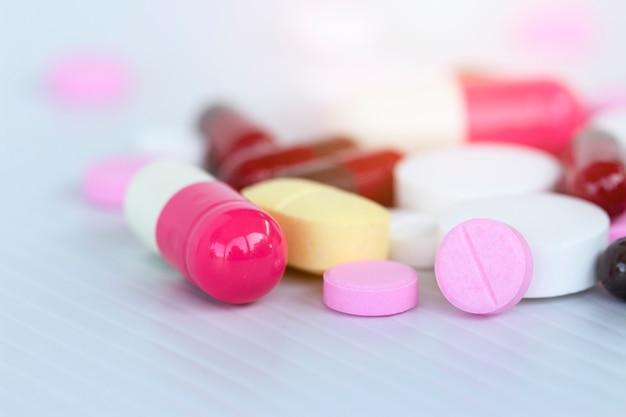 Concetto di medicina; molte medicine colorate. pillole e capsule su sfondo bianco