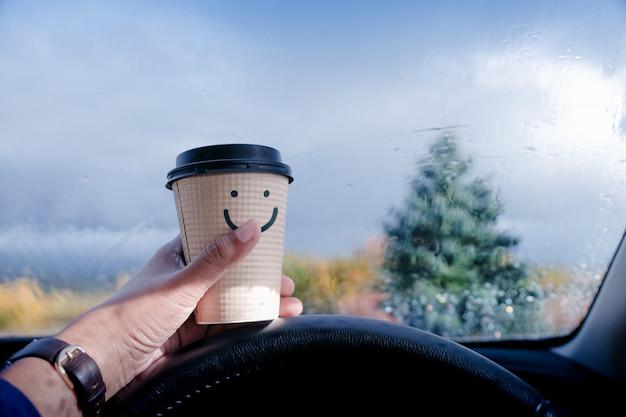 Concetto di mente felice e positiva. autista in possesso di una tazza di caffè con la faccia sorridente cartoon