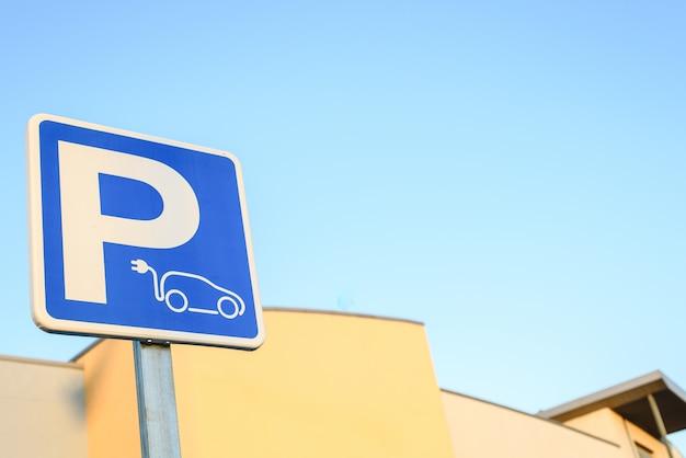 Concetto di mobilità ecologica e zero emissioni. parcheggio di segnale verticale per la ricarica di auto elettriche.
