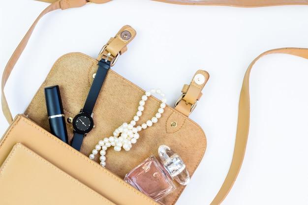 Concetto di moda: borsa da donna con cosmetici, accessori e uno smartphone su bianco