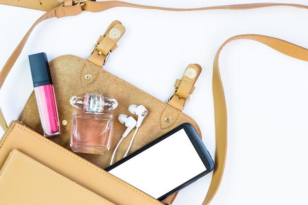 Concetto di moda: borsa da donna con cosmetici, accessori e uno smartphone su uno sfondo bianco. vista piana, vista dall'alto