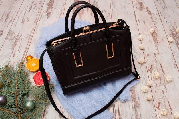 Concetto di moda. borsa da donna nera, maglione caldo, ramo di abete e arancio