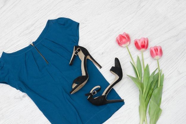 Concetto di moda. camicetta blu, scarpe nere e tulipani rosa. vista dall'alto