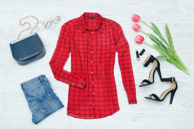 Concetto di moda. camicetta rossa, jeans, borsa, scarpe nere, rossetto e tulipani rosa. vista dall'alto