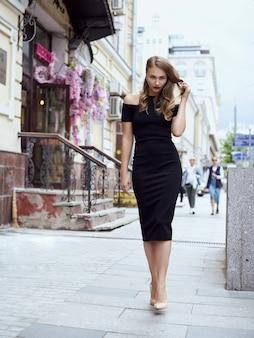 Concetto di moda di strada: corpo pieno ritratto di giovane bella donna che cammina in città.