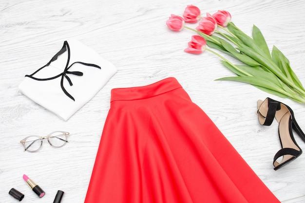 Concetto di moda. gonna rossa, camicetta, occhiali da sole, rossetto, scarpe nere e tulipani rosa. vista dall'alto