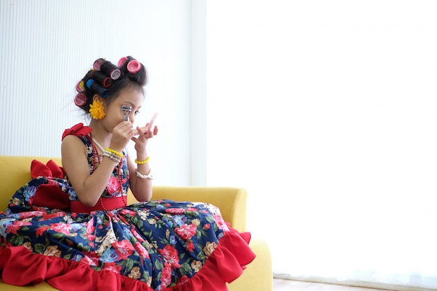 Concetto di moda per bambini. bigodino di prova del ciglio della ragazza asiatica del bambino ed a casa.