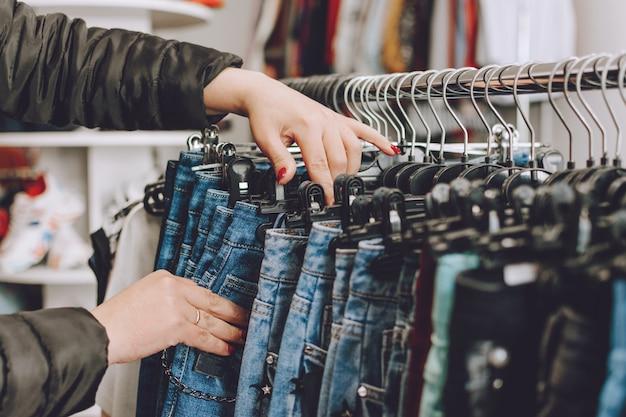 Concetto di moda veloce. la donna sceglie i jeans in un negozio