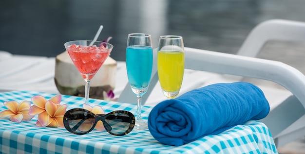 Concetto di momenti di relax, asciugamano blu con cocktail, occhiali da sole accanto alla piscina con un bellissimo fiore di frangipane.