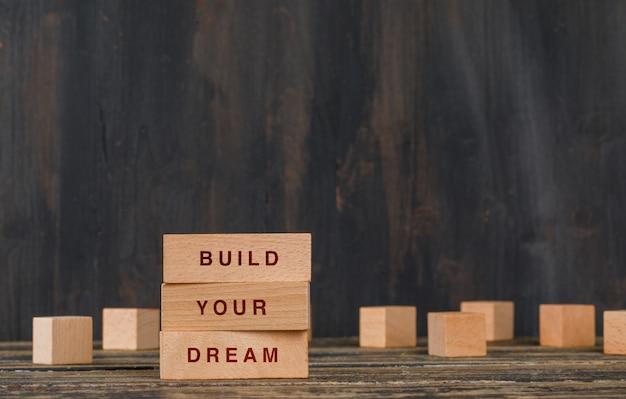 Concetto di motivazione e di affari con i blocchi di legno sulla vista laterale della tavola di legno.