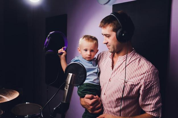 Concetto di musica, di spettacolo, della gente e di voce - cantante maschio con le cuffie e la canzone di canto del microfono allo studio di registrazione del suono.