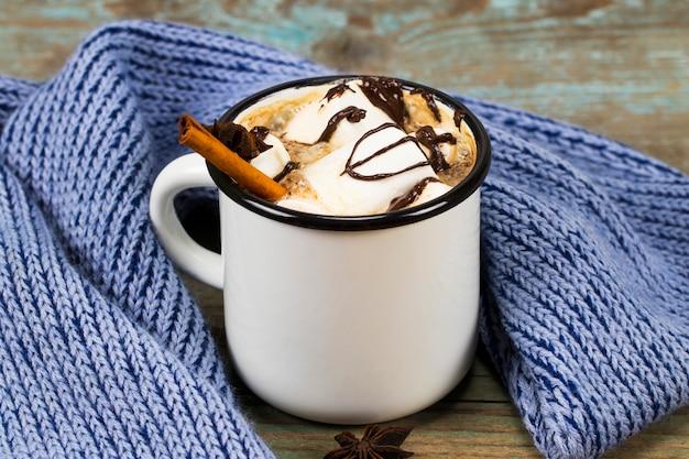 Concetto di natale, cioccolata calda o cacao con marshmallow e spezie, regali di natale, bastoncini di zucchero, ramo di un albero di natale e pigne, sul vecchio tavolo di legno rustico