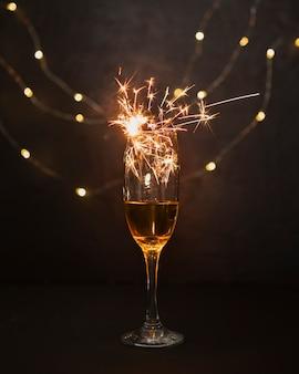 Concetto di natale con bicchiere di champagne e fuochi d'artificio