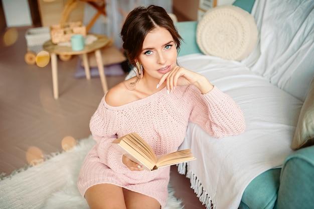 Concetto di natale, di comodità, di svago e della gente - vicino su del libro di lettura felice della giovane donna a casa sopra neve
