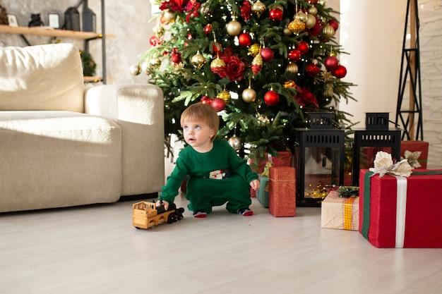 Concetto di natale, di feste e di infanzia - ragazzo sorridente con il contenitore di regalo a casa