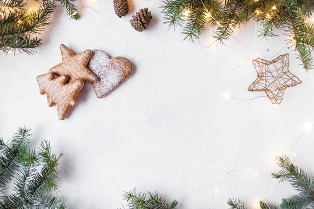 Concetto di natale e capodanno. albero di natale, decorazioni natalizie, biscotti, festoni su luce copia spazio