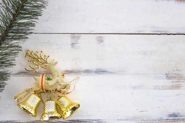 Concetto di natale e festività. chiuda in su degli accessori dorati dell'ornamento di natale delle campane e dei cervi e l'albero del modello sulla vecchia plancia di legno con lo spazio della copia.