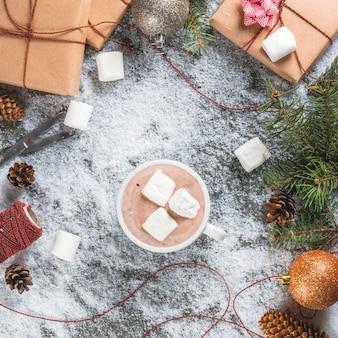 Concetto di natale, fondo della tavola con neve, rami di albero di natale, tazza di cioccolata calda, regali o regali, pigne e decorazione