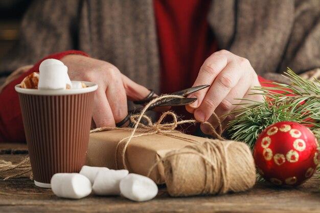 Concetto di natale. mani maschili tenendo presente di capodanno. regali e pergamene confezionati, luogo di lavoro per la preparazione di decorazioni fatte a mano.