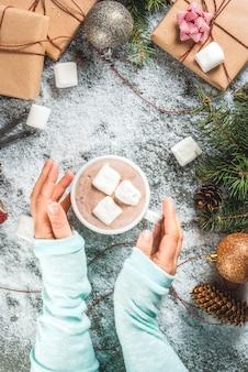 Concetto di natale, sfondo del tavolo con neve, rami di alberi di natale, ragazza tiene una tazza di cioccolata calda con marshmallow, regali o regali, pigne e decorazioni