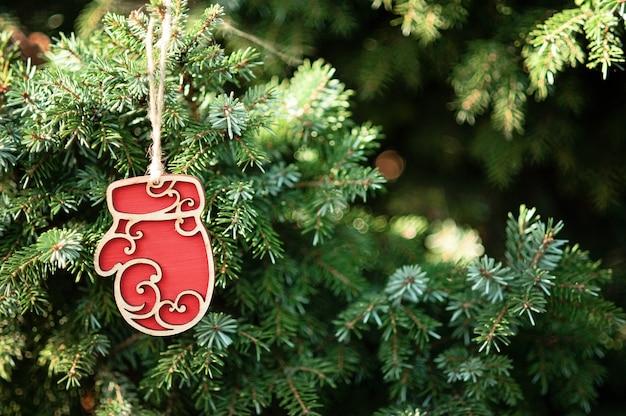 Concetto di natale. sfondo vacanza. giocattolo di legno rosso sui rami degli alberi
