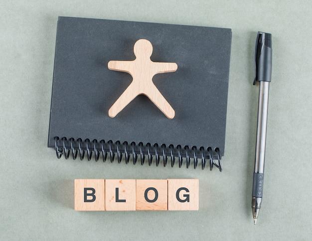 Concetto di note di blog con blocchi di legno, penna e vista dall'alto del taccuino nero.