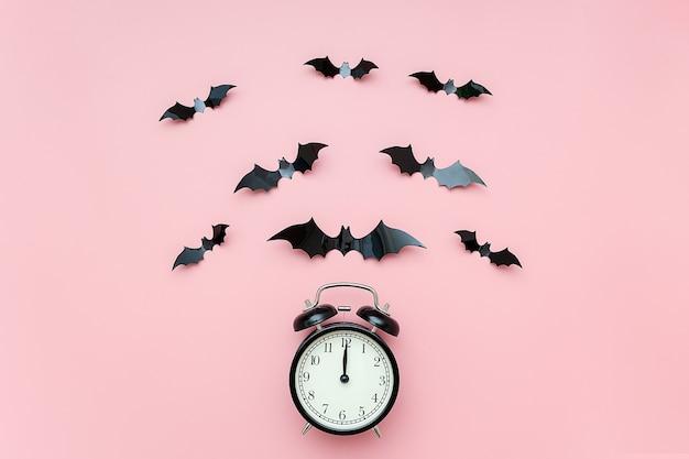 Concetto di notte di halloween. sveglia nera e pipistrelli volanti sul rosa