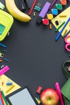 Concetto di nuovo alla scuola di apple zaino cancelleria su sfondo nero.