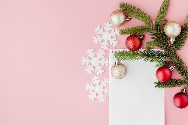 Concetto di nuovo anno. elenco degli obiettivi in blocco note, confezione regalo e decorazioni natalizie su colore pastello rosa con sfondo copyspace