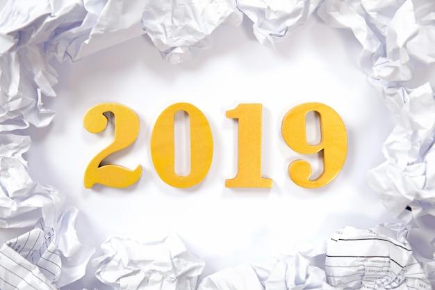 Concetto di nuovo anno. la parola 2019 ha messo su fondo bianco e palle di carta sgualcite